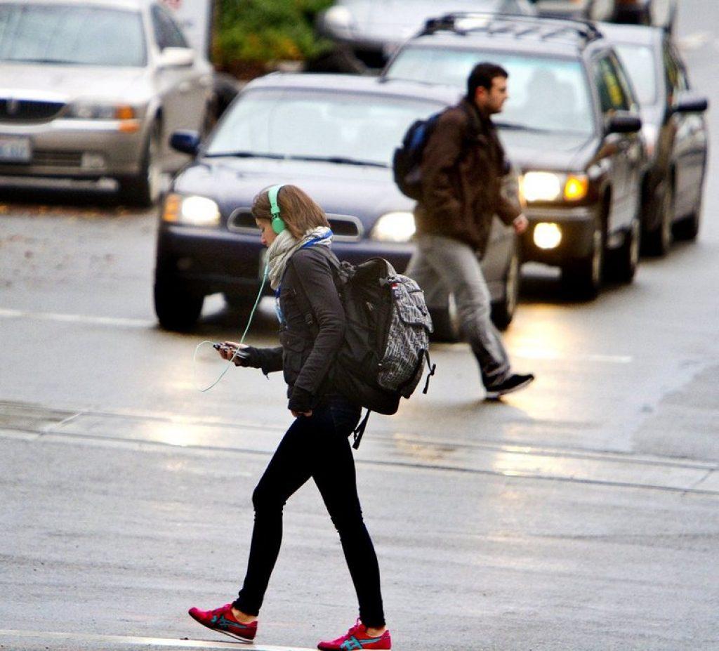 woman crossing street with headphones on